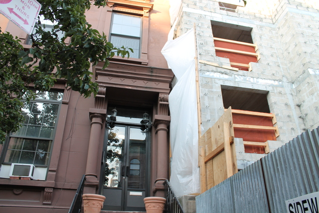 The owner of the brownstone to the left claims in a lawsuit that Abyssinian Development Corporation's construction firm extensively damaged his property.