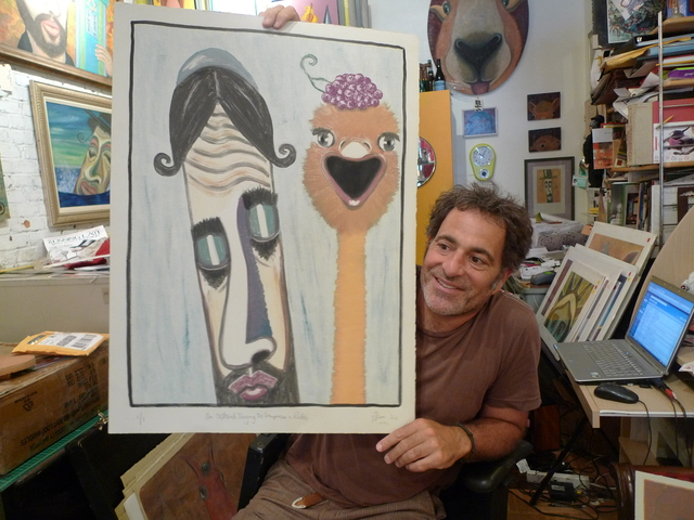 Artist Jonathan Blum with one of his whimsical rabbi portraits at his storefront studio on Park Slope's Fifth Avenue.