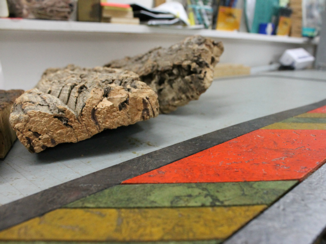 Bark from a cork oak tree beside some colored cork tiles made by Globus Cork.