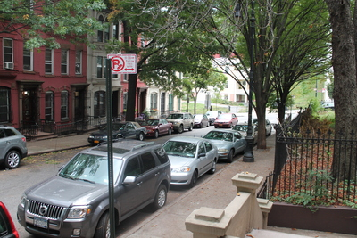 <p>Cars turn onto Hamilton Terrace, a quaint side street, and speed up the block.</p>