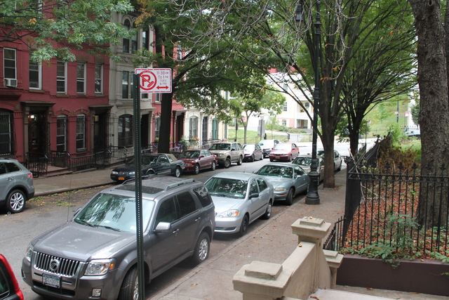 Cars turn onto Hamilton Terrace, a quaint side street, and speed up the block.