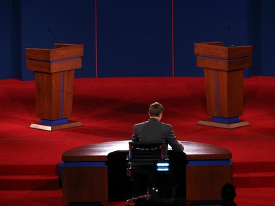 <p>University of Denver student Sam Garry sits at the moderator&#39;s desk before a presidential debate dress rehearsal at University of Denver on Oct. 2, 2012 in Denver, Colo.</p>
