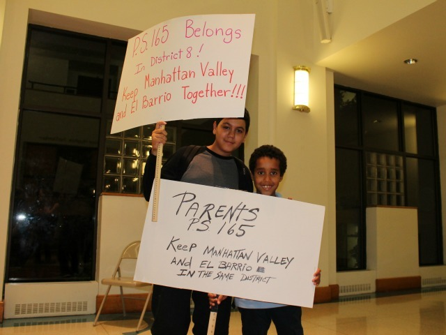 <p>Brothers Dankevin Ynoa, 13, and Dariel Ynoa, 8, held up signs urging the Districting Commission to keep their alma mater in the eighth council district.</p>