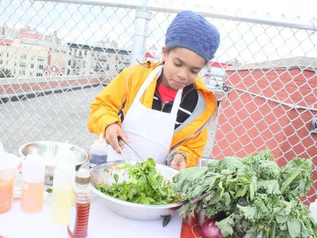 <p>Malik Shahia, a fourth-grader from the Earth School, serves up a salad made with produce mostly from the Fifth Street Farm.</p>