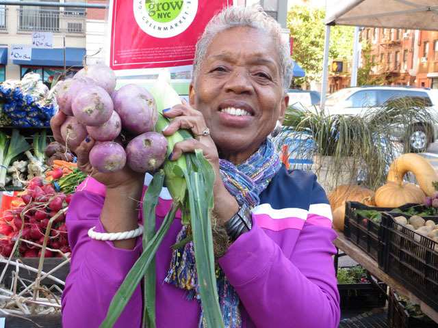 <p>Odessa Jackson shows off her purchases at Harlem's first ever nighttime farmer's market on Oct. 11, 2012.&nbsp;</p>