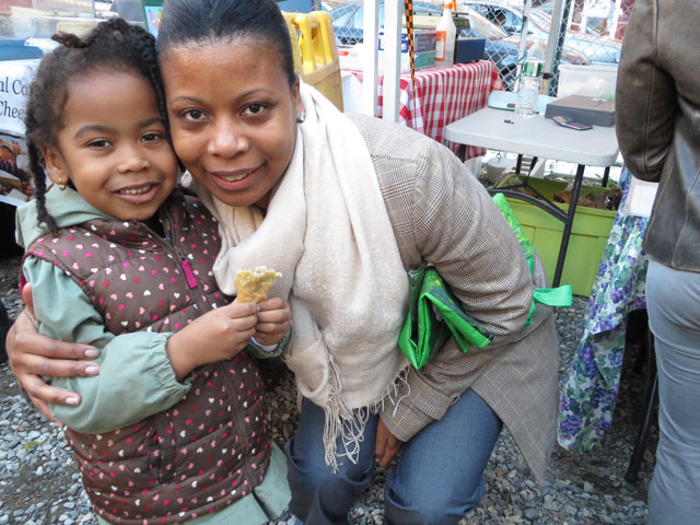 <p>Lakisha&nbsp;Alvarado teaches her daugher, Sade, about food production at Harlem&#39;s first ever nighttime farmer&#39;s market on Oct. 11, 2012.&nbsp;</p>