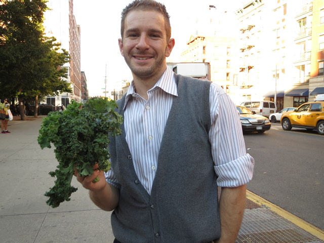 <p>Adam Facher, 26, buys kale and dairy products at Harlem&#39;s first ever nighttime farmers market on Oct. 11, 2012.&nbsp;</p>