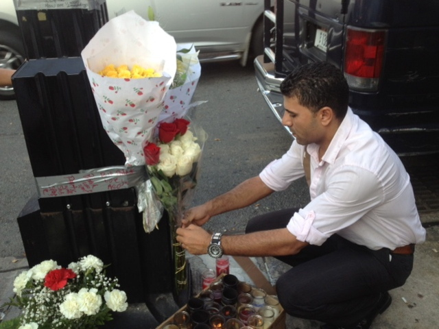 <p>Ashraf Selim, co-owner of The Ice Lounge, places flowers at a memorial for Noel Polanco, who worked at bar. Polanco was shot to death by an NYPD detective on Oct. 4, 2012.</p>