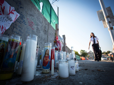 <p>A woman walks past the memorial of Noel Polanco, who was shot and killed by police on Oct. 5, 2012.&nbsp;</p>