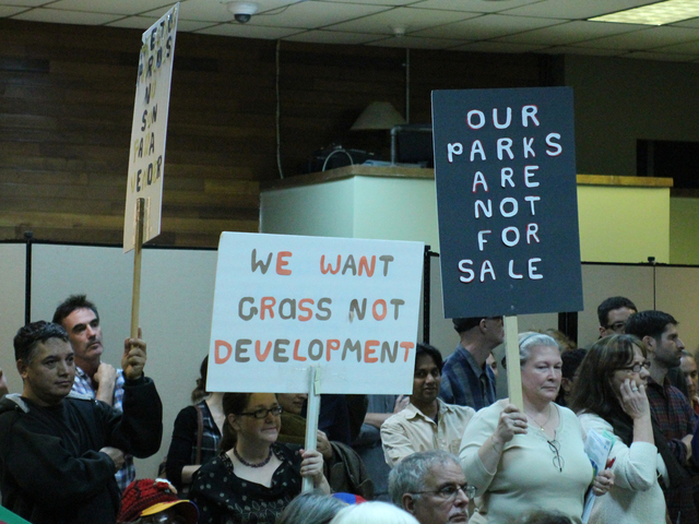 <p>Residents hold signs protesting the planned development for Flushing Meadows Corona Park.</p>