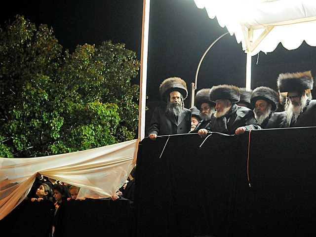 <p>Family members sat on a podium along Bedford Avenue for the wedding of Chaim Hersch Rosenberger and Classoner Rav Scher, Oct. 17, 2012.</p>