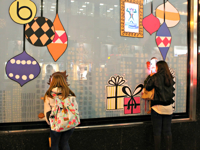 <p>Passersby stop to check out the interactive portion of the holiday windows, which snap photographs of people and project their images onto characters inside the windows.</p>