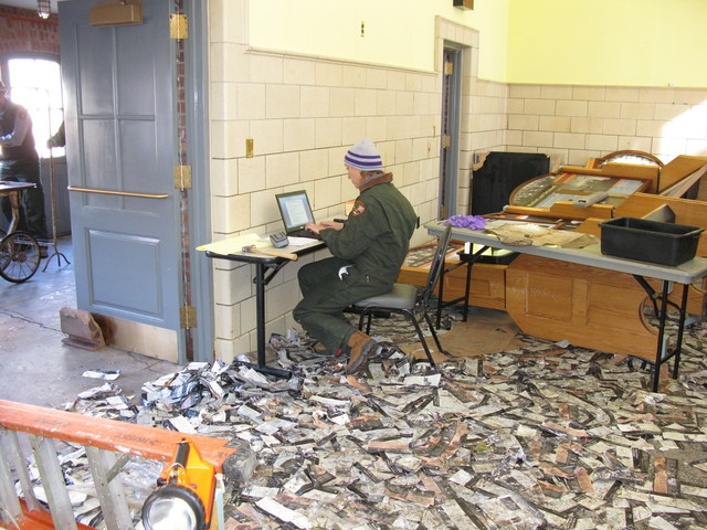 <p>A Parks worker documents Hurricane Sandy damage amid a carpet of brochures strewn about by floods.&nbsp;</p>