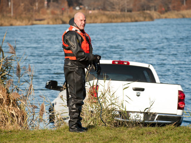 <p>An Emergency Service Unit officer prepares to attach chains to the pickup Monday morning, Nov. 19, 2012.</p>