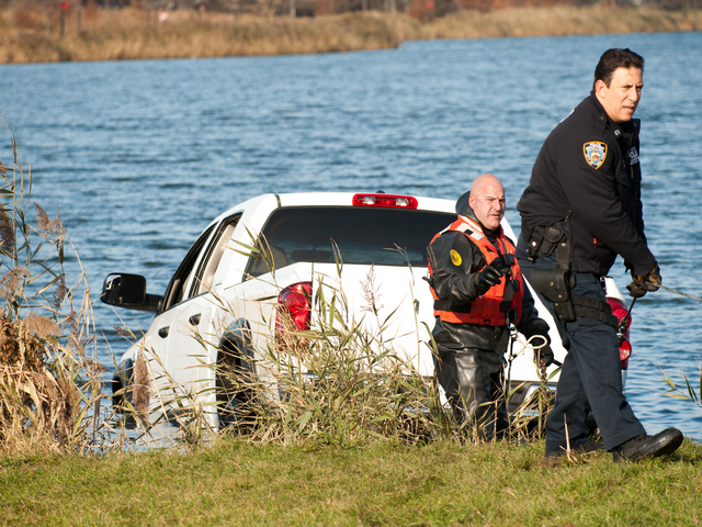 <p>Officers work to remove the pickup from Meadow Lake in Forest Hills Monday morning, Nov. 19, 2012.</p>