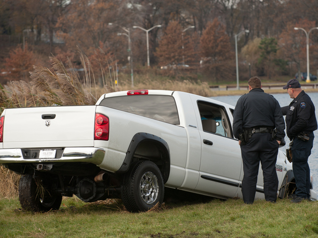 <p>Officers stand next to the pickup truck as it&#39;s removed from Meadow Lake in Forest Hills Monday morning, Nov. 19, 2012.</p>