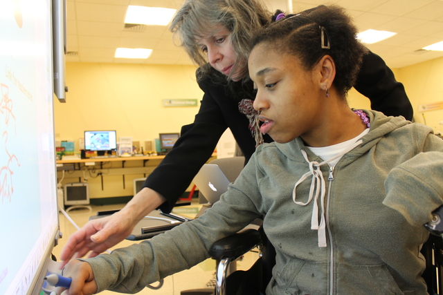 <p>Liz Voluz, director of assisted technology, works with Schevon Williams, 32, at an electronic learning device at United Cerebral Palsy of New York City.</p>