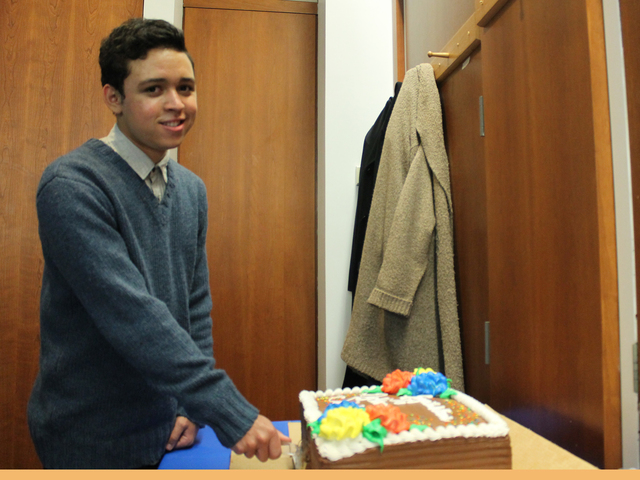 <p>Jean-Franco Diaz smiles as he cuts a cake honoring the Dyckman Institute Scholars on Nov. 27.</p>