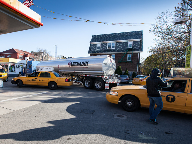 <p>An attendant at the Shell gas station on Northern Blvd., Queens directs yellow cabs to the fuel pumps on Nov. 9, 2012.</p>