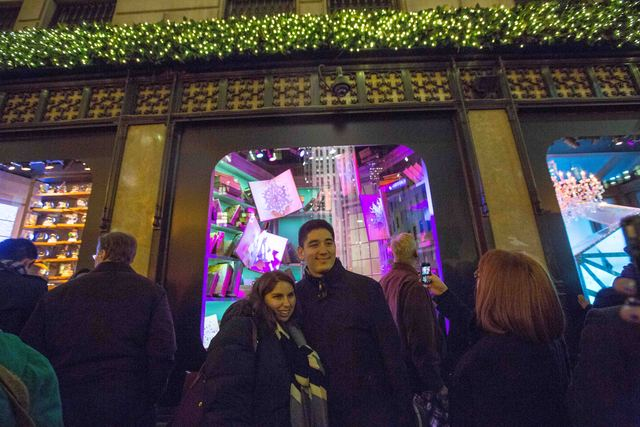 <p>Visitors take pictures in front of the Saks&#39; windows on Nov. 19.</p>