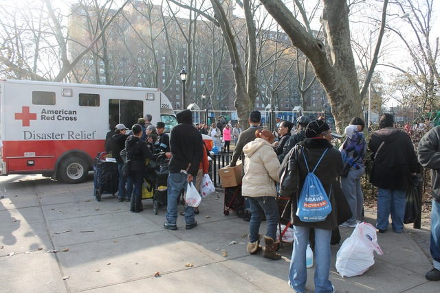 <p>Red Hook Houses residents wait in line to receive water and other supplies from a Red Cross distribution truck.</p>
