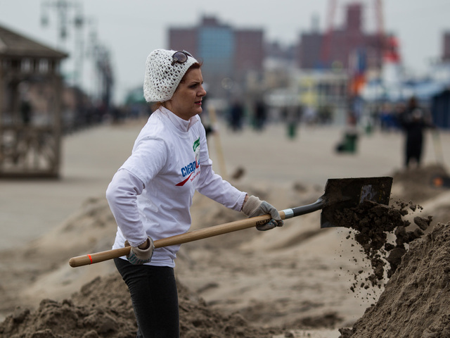 <p>A local volunteer helps with the Coney Island Beach cleanup on Nov. 10, 2012.</p>