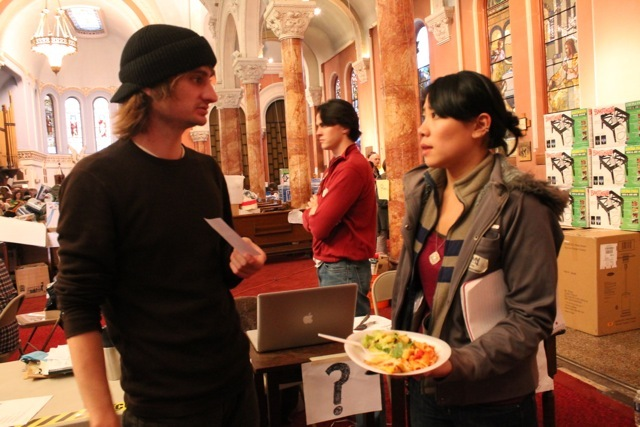<p>November 12, 2012 -Organizer Amy Weng talks with another volunteer while eating her lunch prepared by volunteers in the church kitchen.</p>