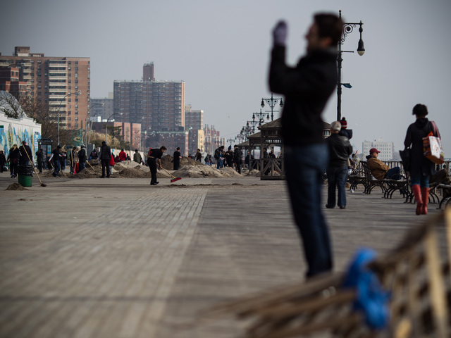 <p>Parks Dept. volunteers help with the Coney Island Beach cleanup while a tourist takes pictures on the boardwalk on Nov. 10, 2012.</p>
