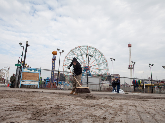 <p>A volunteer helps with the Coney Island Beach cleanup on Nov. 10, 2012.</p>