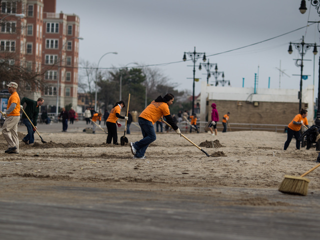 <p>Volunteers from the New York Cares organization sweep away sand from Brighton Beach on Nov.10, 2012.</p>