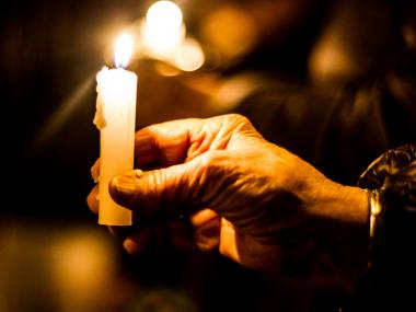 A woman holds a candle at a vigil for the victims of Sandy Hook Elementary School on West 72nd Street and Riverside Drive, Dec. 15, 2012.