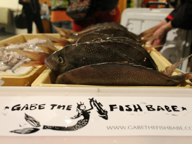 <p>A &quot;Gabe the Fish Babe&quot; sticker next to fish from the company&#39;s supply.</p>
