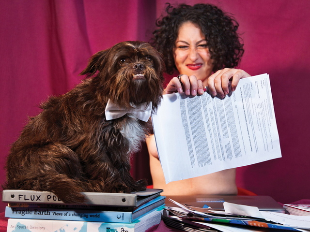 <p>Flux Factory executive director Christina Vasallo poses as a sultry Ms. April who rails against the IRS by ripping up her faux tax bills, along with Flux mascot pup Truman.</p>