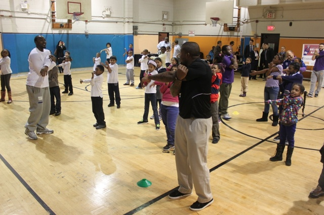 <p>Hakeem Nicks stretches with kids from Union Settlement.</p>