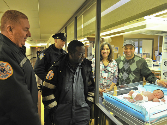 <p>Abdel Elkarhat showed off his newborn son, Nassim, as Port Authority Tunnel and Bridge Agents George McCann (left) and Jean Bernard look on. The child was born in the Holland Tunnel on Wednesday, Dec. 26, 2012.</p>