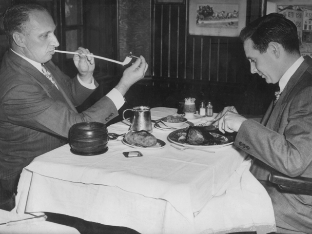 <p>Men smoking churchwarden pipes at Keens Steakhouse.</p>