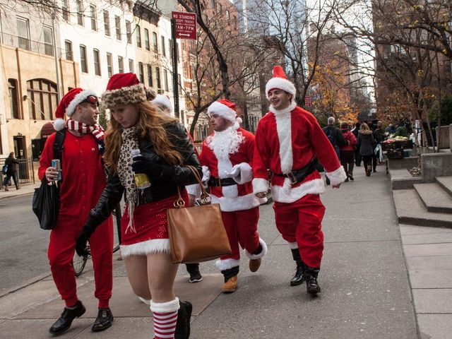 <p>People dressed as Santa walk down the street during SantaCon 2012.</p>