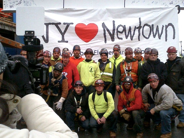 <p>Construction workers photographed at a ceremony Dec. 17, 2012 attached a banner in honor of Newtown massacre victims to the final steel beam.</p>