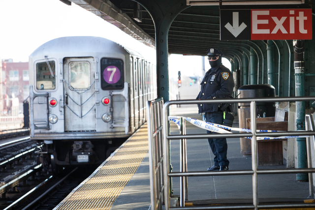<p>A police officer stands watch as a 7 train approaches 40th Street Station in Sunnyside Friday morning, Dec. 28, 2012.</p>
