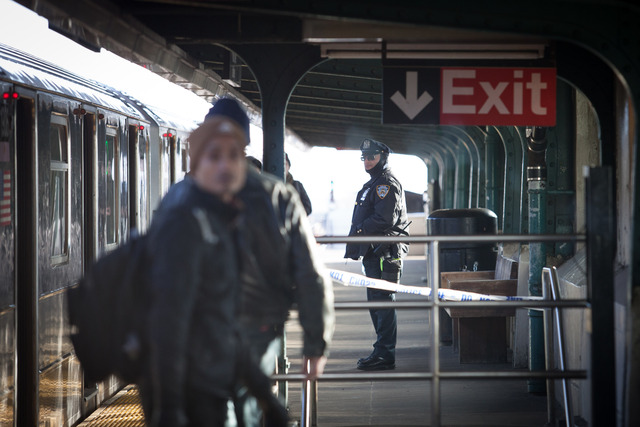 <p>Subway riders exit a 7 train at 40th Street Station in Sunnyside as a police officer stands watch Friday morning, Dec. 28, 2012.</p>