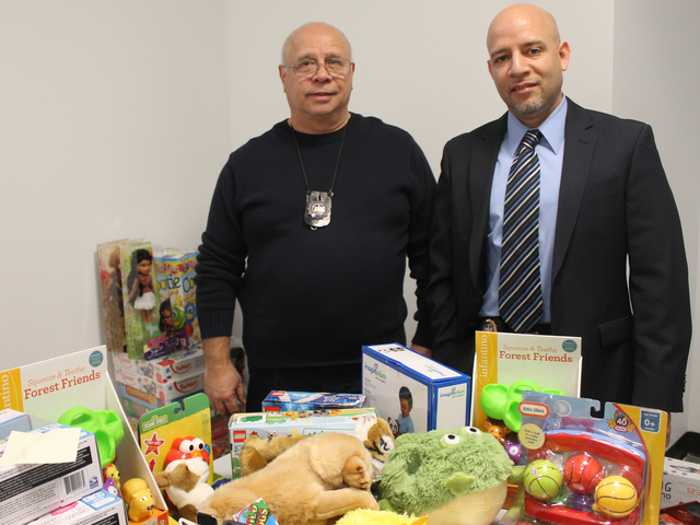 <p>Lieutenants Robert Vittuci and Benny Castillo, court officers at the Red Hook Community Justice Center, stand behind a table piled with toys they collected for needy Brooklyn children.</p>