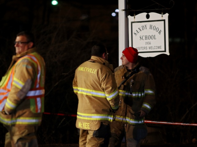 <p>Emergency workers stand in front of the Sandy Hook School December 14, 2012 in Newtown, Connecticut.</p>
