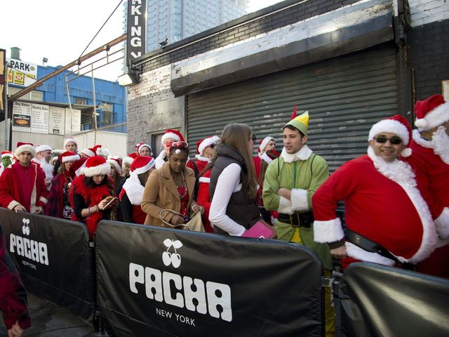 <p>Santas wait outside of Pacha, a nightclub in Hell&#39;s Kitchen, during SantaCon 2012.</p>