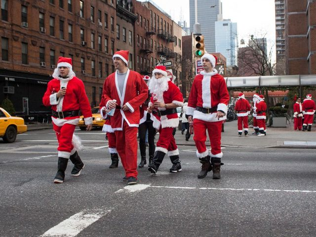 <p>People dressed as Santa walk down the street during SantaCon&nbsp;2012.</p>