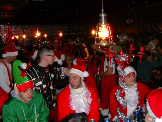 <p>Santas enjoy time in a bar during SantaCon.</p>