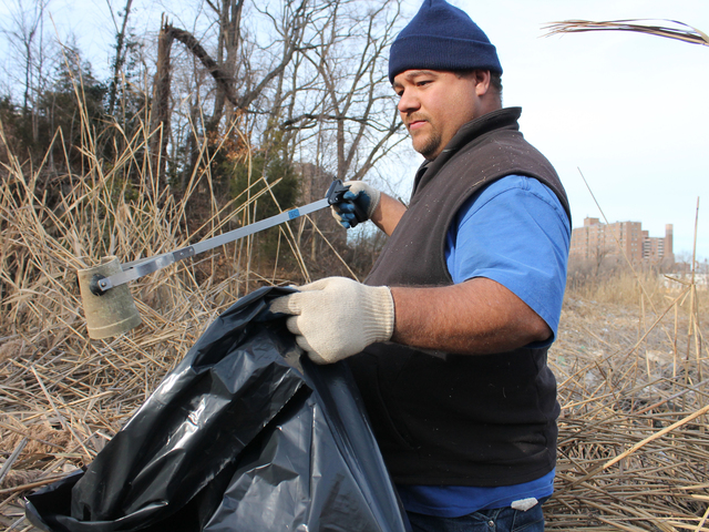<p>Edwards Santos picks up trash along the Sherman Creek shoreline.&nbsp;</p>