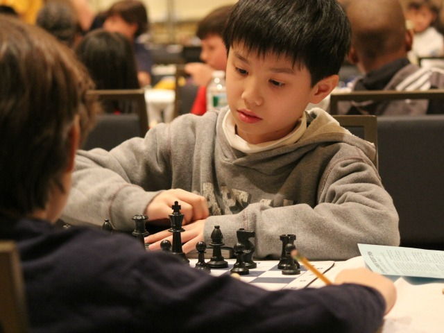<p>Spencer Ha, a nationally ranked chess player, makes a move.</p>