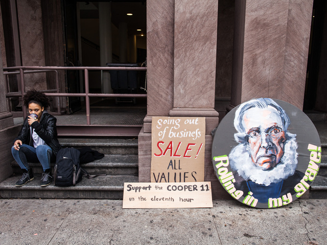 <p>A student outside the Cooper Union school sits next to protest signs on Dec. 8, 2012.</p>