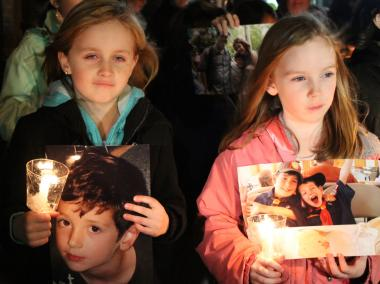 Local children marched with photos of 6-year-old Benjamin Wheeler, who was killed in the Newtown school shooting, at a candlelight vigil in Sunnyside, Queens on Tuesday, Dec. 19.