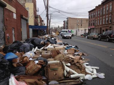 RED HOOK — A half-block-long pile of rotting wood, cardboard, overflowing trash bags and other refuse has sat on  Red Hook's  main commercial thoroughfare for weeks, spilling across the street and sidewalk as it awaits pickup by the city's  Department of Sanitation .
